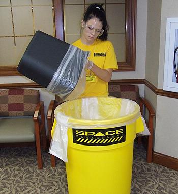 Space Management employee handling trash